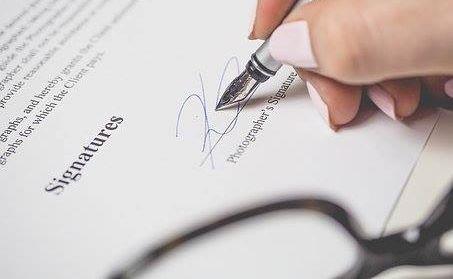 man signing on paper